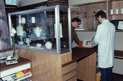 To menn ser i en perm ved skranken på Hemne apotek i Kyrksæterøra