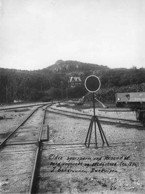 Sporsperresignal på Kristiansand stasjon med lokomotivstall eller verksted i bakgrunnen