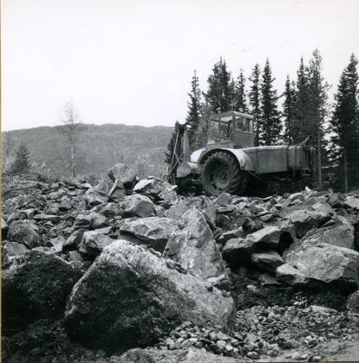 Gravemaskin på steintipp.