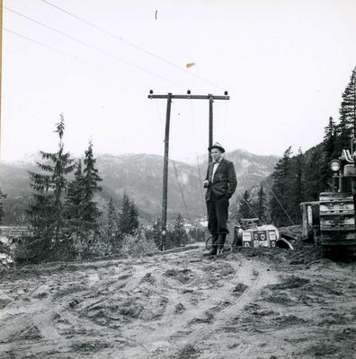 Mann ved kraftline, buldoser i bakgrunnen.