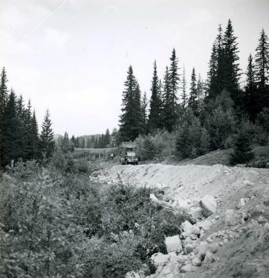 Lastebil lagar veg i skogen.