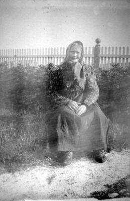 En dame sitter ute i solskinnet en sommerdag i Arthur og Kirstens Bucks hage på Hasvik