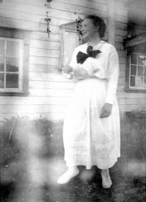 En dame står foran et hus