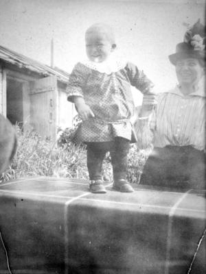 Et lite barn står oppe en kasse/eske i solskinnet