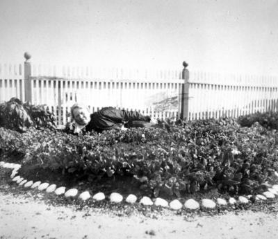 En dame med mørke klær ligger i et blomsterbed en solskinnsdag i Arthur og Kirsten Bucks hage
