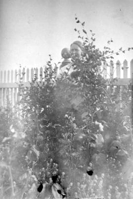 En dame står delvis skjult bak en høy plante i Arthur og Kirsten Bucks hage
